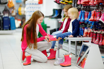 Young family of three choosing new rain boots