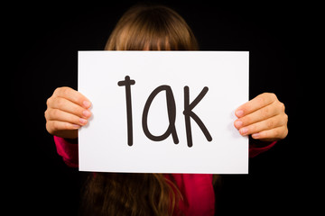 Child holding sign with Danish word Tak - Thank You