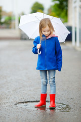 Adorable little girl holding white umbrella