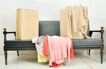 cardboard boxes and stack of clothes on a black sofa