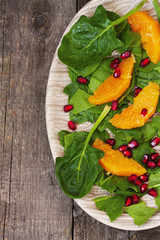 spinach salad, orange and pomegranate on a wooden background
