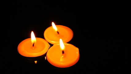 Candles burning in the dark,slowly floating on water