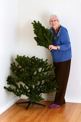 senior woman with fake christmas tree