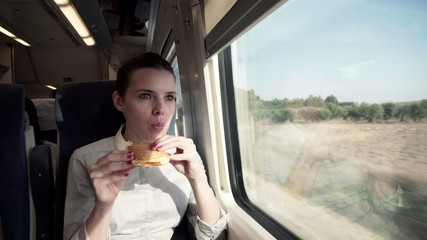 Young businesswoman eating sandwich during train ride