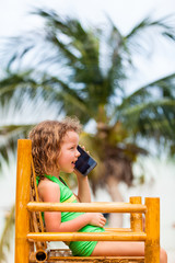 Girl in bathing suit talking on mobile