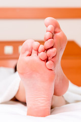 barefoot female feet resting in bed