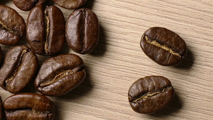 Coffee beans come out of the darkness. Moving shadows.