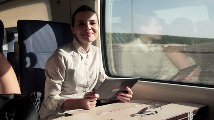Portrait of happy businesswoman with tablet on a train