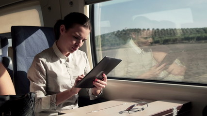 Young businesswoman working with tablet during train ride