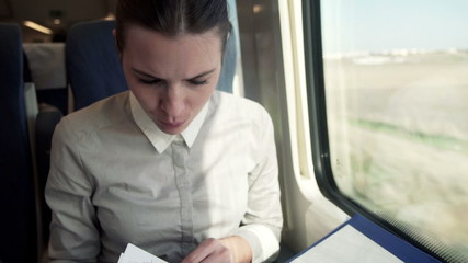 Young businesswoman signing documents during train ride