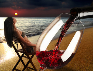 Woman at the sunset on the beach with a glass of red wine