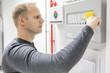Technician test fire panel in data center - 73978806