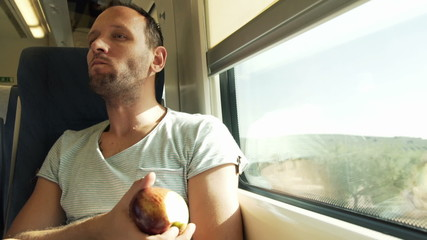 Young man eating tasty apple on a train