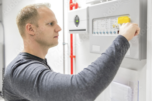 Technician test fire panel in data center - 73978806