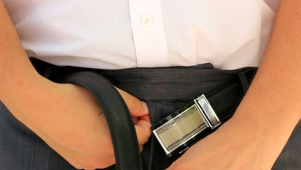 Man fastening belt on his trousers