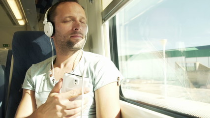 Young, handsome man listening to the music during train travel