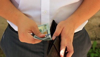 Man taking money and putting them in his wallet