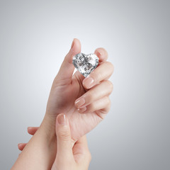 hand holding 3d diamond over grey background