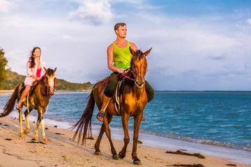 Vacation Lifestyle. Couple Horseback Riding at Sunset