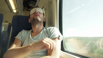 Young man with sleeping eye mask on a train