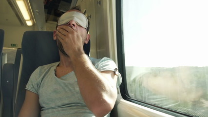 Man with sleeping eye mask wake up from nap on a train