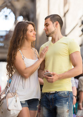 Couple with smartphone at street