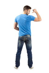 Man pointing with thumb on shirt. Rear view.