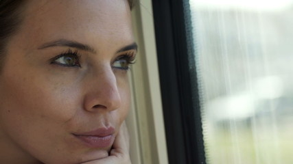 Face of woman looking through the window during train ride