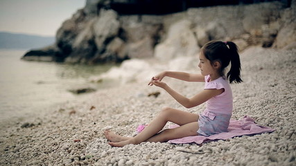 Child sits on the beach and throwing stones into the water.
