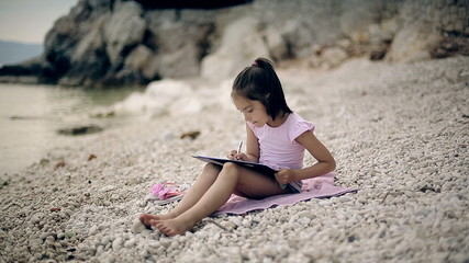 A child sits on a beach near the Adriatic Sea and draws