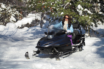 Beautiful girl sitting on a snowmobile in the winter forest