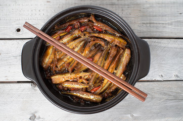 Vietnamese caramelized smelt fishes in clay pot on a wooden tabl