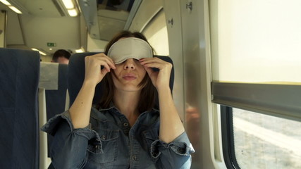 Young woman with sleeping eye mask on a train
