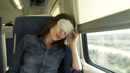 Pretty woman with sleeping eye mask on a train