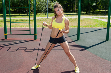 Beautiful woman is doing some exercises with gym band