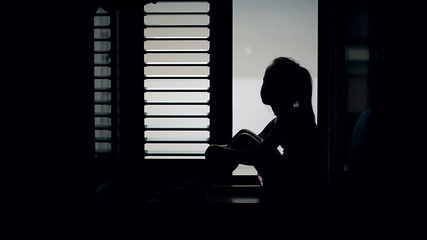 Silhouette of a child who is sitting on the sill