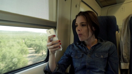 Young woman with smartphone eating apple on a train