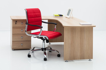wood desk and red armchair