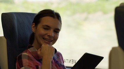 Portrait of beautiful, smiling woman with tablet during train ri