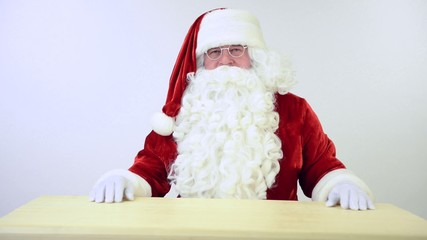 Santa Claus sitting at the table and gestures. on a white