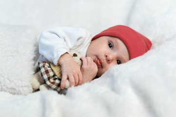 baby in red hat shows tongue