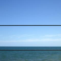 Ocean through wire fence