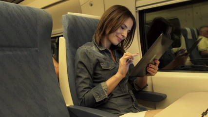 Young woman with tablet sitting on a train in the night