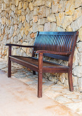 Street wooden bench against brick wall.