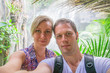 Attractive couple doing selfie in jungle.