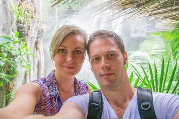 Attractive couple doing selfie in jungle.
