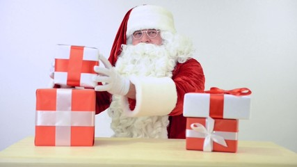 Santa Claus sitting at the table with gifts boxes. on a white