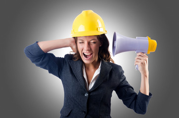 Female construction worker with loudspeaker