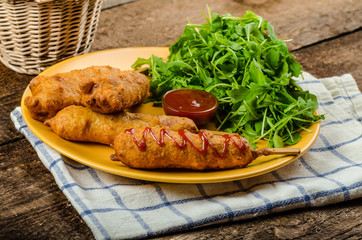 Corn dog with fresh arugula salad and hot dip