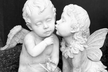 kissing couple of angelic figurines  isolated on dark background